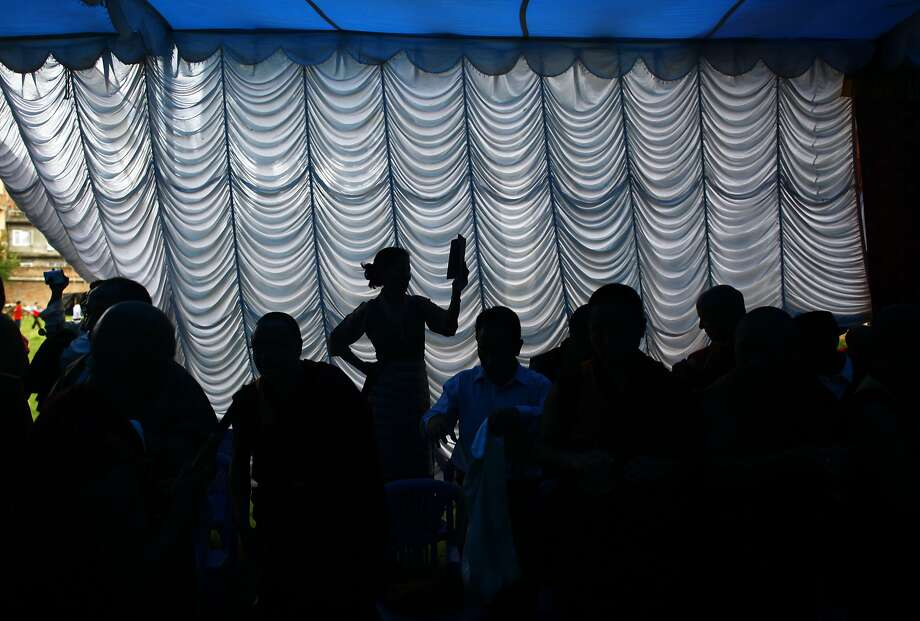 A Tibetan woman, center, is silhouetted with others as she takes photographs with a mobile device during celebrations to mark the birthday of their spiritual leader the Dalai Lama in Katmandu, Nepal, Sunday, July 6, 2014. (AP Photo/Niranjan Shrestha) Photo: Niranjan Shrestha, Associated Press