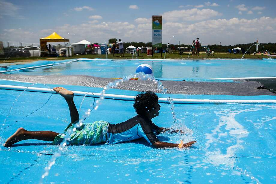 Steffon Nzerem, 6, of Shreveport, La., makes his way down the tarp slide at the Shelby Farms Park Conservancy's inaugural Splash and Splatter water festival Sunday July 6, 2014, in Memphis, Tenn. The water festival has a splash pad, water slides, and sand castle sculpting areas. Splash and Splatter will continue through the rest of July.    (AP Photo/The Commercial Appeal, William DeShazer) Photo: William DeShazer, Associated Press
