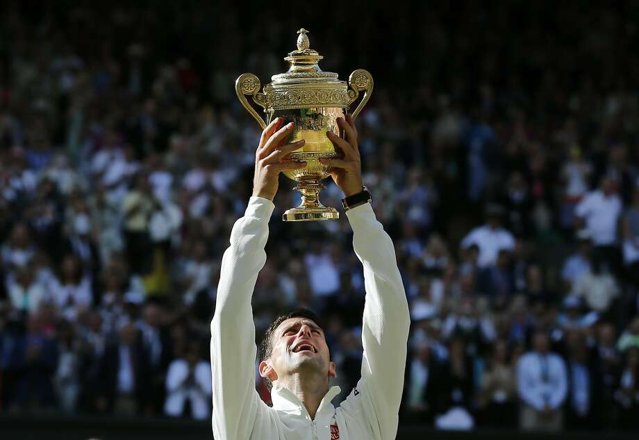 Novak Djokovic of Serbia holds up the trophy after defeating Roger Federer of Switzerland in the men's singles final at the All England Lawn Tennis Championships in Wimbledon, London, Sunday July 6, 2014. (AP Photo/Ben Curtis) Photo: Ben Curtis, Associated Press