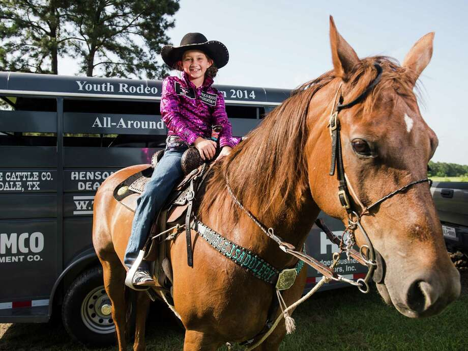Chloe Little, 8, poses for a photo atop Charlotte, one of her American quarter horses, at her family's home in Mauriceville on Monday afternoon. Little beat out 150 competitors and won a horse trailer at the Youth Rodeo Association finals, the biggest organization of its type in Texas. Photo taken Monday 6/30/14 Jake Daniels/@JakeD_in_SETX Photo: Jake Daniels / ©2014 The Beaumont Enterprise/Jake Daniels