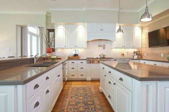 "For a look that was quaint but ""not too rustic,"" designer Peggy Hull kept the kitchen clean with white cabinets and subway tiles amd brushed nickel light fixtures and pulls."