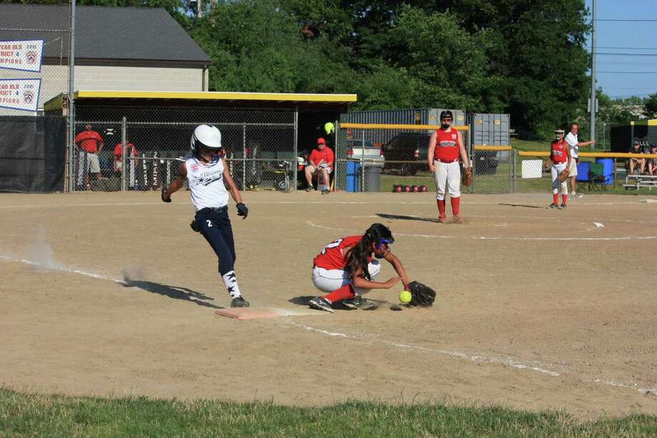 Westport Little League softball's Ali Green, left, is safe at first after a bobble by Redding/Easton's first baseman in a game on Sunday. Redding/Easton won 3-1, ending Westport's season. Photo: Rosanna Alfero/Contributed Photo / Westport News Contributed