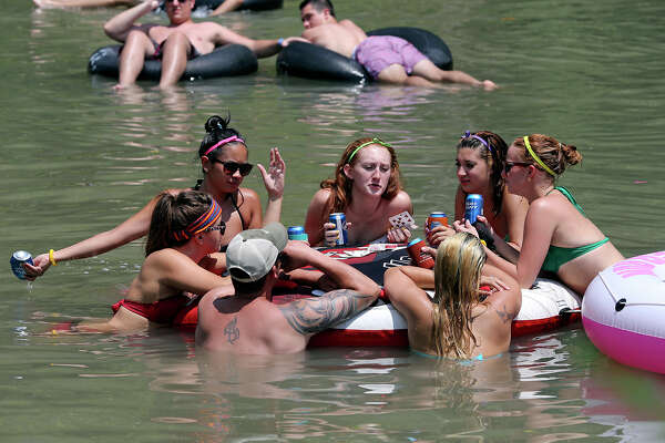 A group from Austin plays cards and enjoys beverages in the water as enthusiasts cool down in the Guadalupe River near New Braunfels on July 6, 2013.