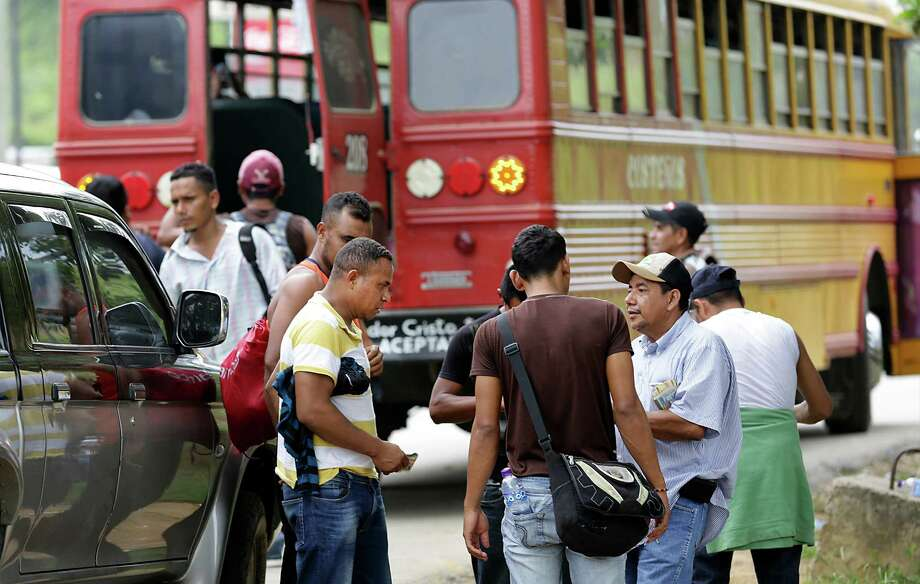 The man at right collects money as he sells bus tickets to deported Hondurans that were dropped off in Corinto, Honduras at the Guatemala border. Friday, June 27, 2014. The bus will take them to San Pedro Sula where they live, or will continue their journey to their home town. Photo: Bob Owen, San Antonio Express-News / ©2013 San Antonio Express-News