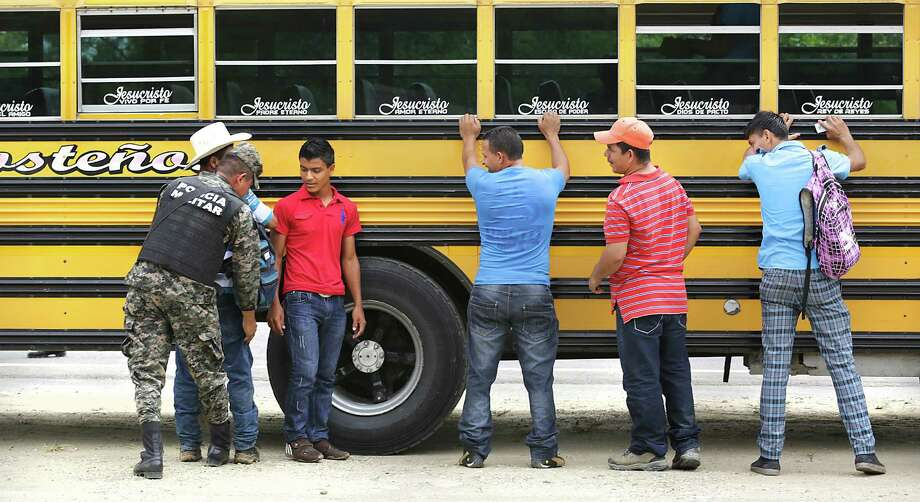 Male bus passengers are searched by Honduran Military Police at a military check point near Corinto, Honduras at the Guatemala border. They were allowed to pass but still had to present papers to immigration at the border.  Friday, June 27, 2014. Photo: Bob Owen, San Antonio Express-News / ©2013 San Antonio Express-News