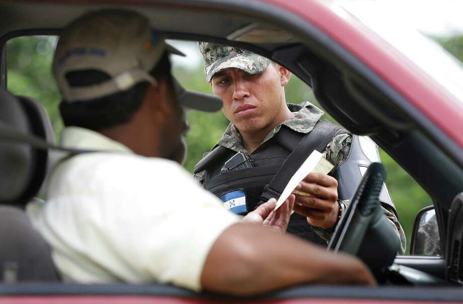 A Honduran Military Police officer checks the papers of passengers in a vehicle traveling to Guatemala, near Corinto, Honduras at the Guatemala border. Friday, June 27, 2014. Photo: Bob Owen, San Antonio Express-News / ©2013 San Antonio Express-News