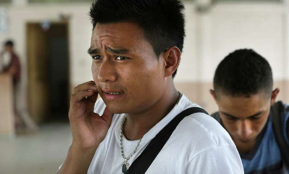 Osmedi Guerra, center, who claims to be a cousin of Evin Salvapena, right, ponders what to do, after Salvapena was turned away from crossing the border into Guatemala because he is underage, in Corinto, Honduras. Friday, June 27, 2014. Photo: Bob Owen, San Antonio Express-News / ©2013 San Antonio Express-News