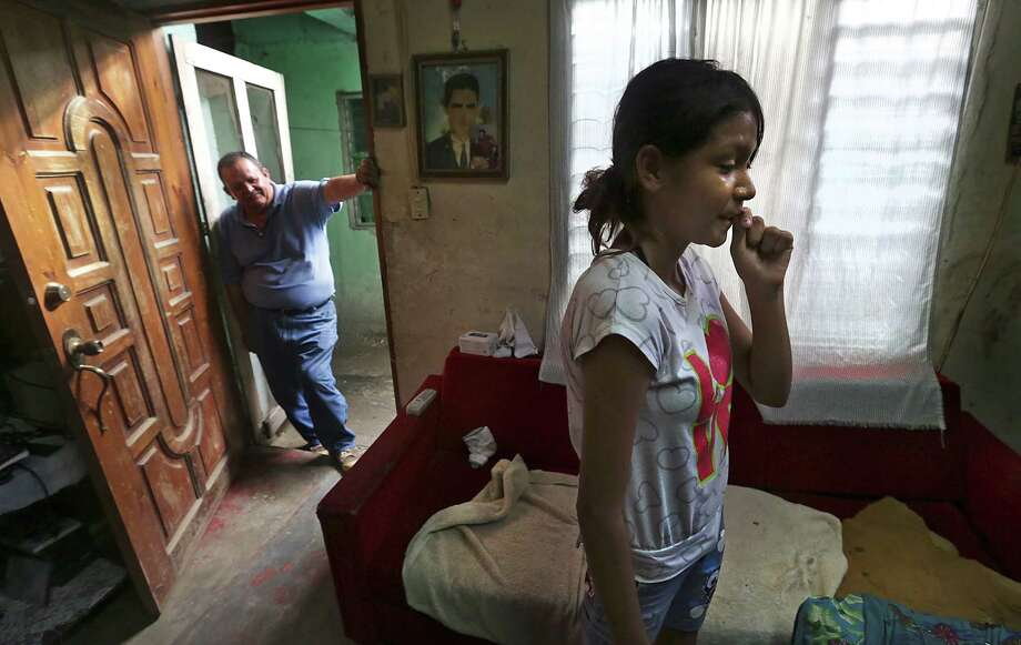 Keyla Galeano, right, 12, who was recently deported from Mexico with her 30 year-old mother Fany Galeano, arrived back in her home town of San Pedro Sula, Honduras last night, having been apprehended in Veracruz, MX.  Her mother is already planning an attempt to go to Houston, TX, again where family members live. Thursday, June 26, 2014.  Jose Alvarado, Keyla's father who is divorced from Galeano, waits for her in the doorway. Photo: Bob Owen, San Antonio Express-News / ©2013 San Antonio Express-News