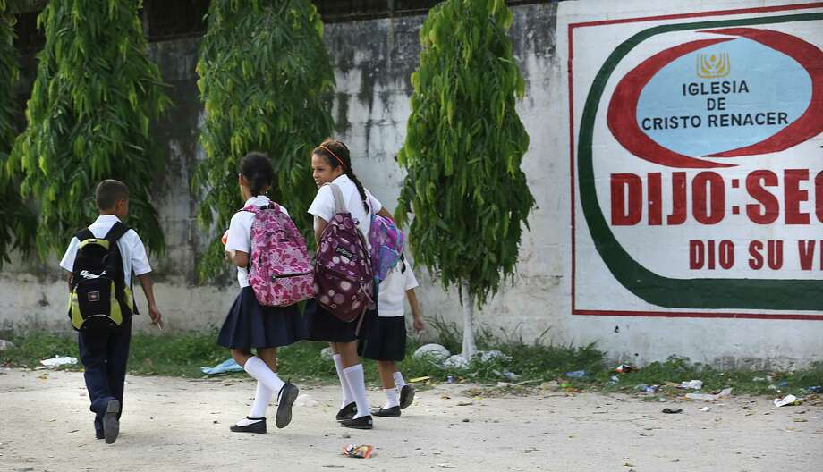 Elementary school children walk home in Bario Satelite where Fany Galeano and her 12 year-old daughter Keyla live. Recently, Mexico deported Galeano, 30, and her daughter, who arrived back in their home town of San Pedro Sula, Honduras last night, having been apprehended in Veracruz, MX. Galeano is already planning another attempt to reach Houston, TX, where family members live.  Thursday, June 26, 2014. Photo: Bob Owen, San Antonio Express-News / ©2013 San Antonio Express-News