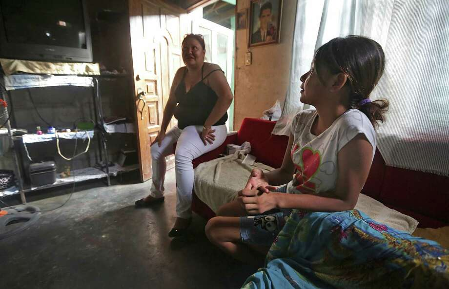 Keyla Galeano, 12, right, listens to her 30 year-old mother Fany Galeano, talk about trying again to reach the U.S. Recently, Mexico deported Galeano, and her daughter Keyla, who arrived back in her home town of San Pedro Sula, Honduras last night, having been apprehended in Veracruz, MX.  She is already planning an attempt to go to Houston, TX, where family members live. Thursday, June 26, 2014. Photo: Bob Owen, San Antonio Express-News / ©2013 San Antonio Express-News