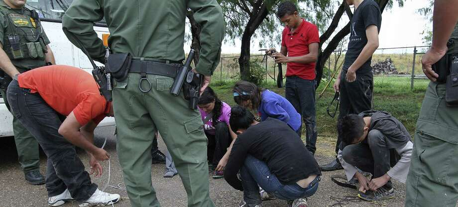 Immigrants remove their shoelaces as U.S. Border Patrol agents processed them in the Texas community of Granjeno. / ©2014 San Antonio Express-News