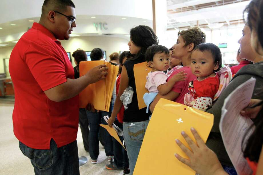 JUNE 26, 2014, 3:17 PM, MCALLEN, TEXAS - Bus employee Daniel Villicana hands out manila envelopes to newly released immigrants from Central America. U.S. Immigration Services drops off the immigrants from Central America at bus stations after they are processed at the detentions center. They have orders to appear before an immigration judge at their final destination in this country. Photo: Jerry Lara, San Antonio Express-News / ©2014 San Antonio Express-News