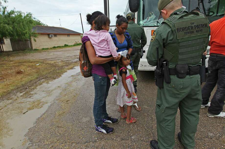 "JUNE 25, 2014, 5:02 PM, GRANJENO, TEXAS – Immigrants wait to board a U.S. Government bus as Border Patrol agents process them in Granjeno, Texas. The city is just north of  ""El Rincon del Diablo,"" the Devil's Corner, a hotbed of illegal border crossing on the Rio Grande by juvenile and mothers with children immigrants from Central Photo: Jerry Lara, San Antonio Express-News / ©2014 San Antonio Express-News"