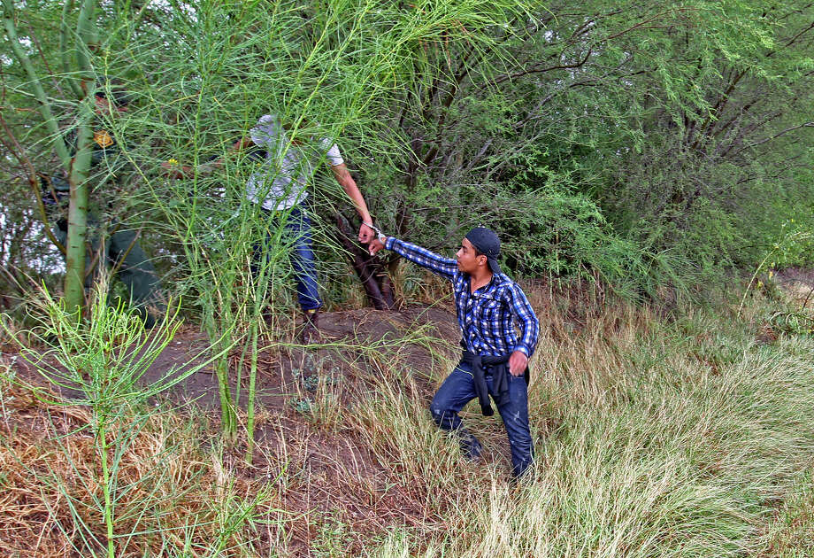 JUNE 25, 2014, 12:25 PM, HIDALGO, COUNTY – Immigrants are led out of a field by a U.S. Border Patrol agent on Shuerbach Road near Bentsen Rio Grande Valley State Park. Photo: Jerry Lara, San Antonio Express-News / ©2014 San Antonio Express-News
