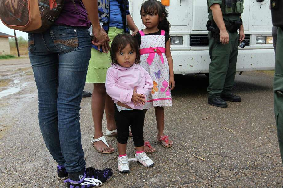"""JUNE 25, 2014, 5:04 PM, GRANJENO, TEXAS – Immigrants children wait with parents as Border Patrol agents process them in Granjeno, Texas. The city is just north of  """"El Rincon del Diablo,"""" the Devil's Corner, a hotbed of illegal border crossing on the Rio Grande by juvenile and mothers with children immigrants from Central America. Photo: Jerry Lara, San Antonio Express-News / ©2014 San Antonio Express-News"""