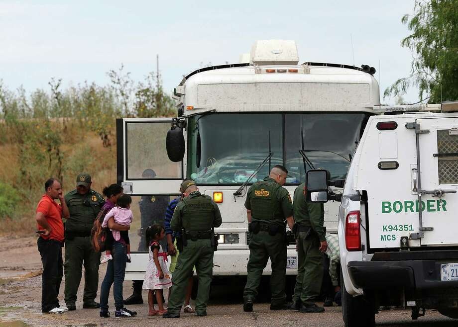 "JUNE 25, 2014, 5:02 PM, GRANJENO, TEXAS – A U.S. Government bus waits to transport immigrants being processed by Border Patrol agents in Granjeno, Texas. The city is just north of  ""El Rincon del Diablo,"" the Devil's Corner, a hotbed of illegal border crossing on the Rio Grande by juvenile and mothers with children immigrants from Central America. Photo: Jerry Lara, San Antonio Express-News / ©2014 San Antonio Express-News"