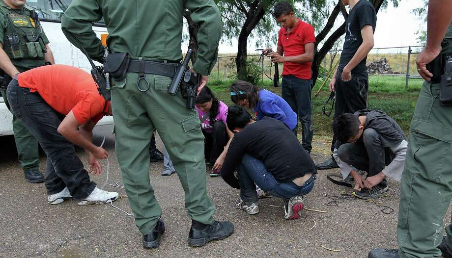 "JUNE 25, 2014, 5:02 PM, GRANJENO, TEXAS - Immigrants remove shoelaces as U.S. Border Patrol agents processed them in Granjeno, Texas. The city is just north of  ""El Rincon del Diablo,"" the Devil's Corner, a hotbed of illegal border crossing on the Rio Grande by juvenile and mothers with children immigrants from Central America. Agents confiscate the immigrants' shoelaces to keep them from harming themselves. Photo: Jerry Lara, San Antonio Express-News / ©2014 San Antonio Express-News"