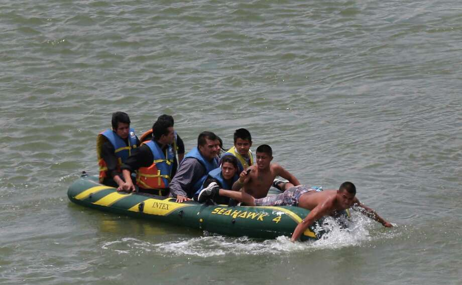 JUNE 24, 2014, 2:02 PM, ROMA, TEXAS - Using an inflatable raft, coyotes, or smugglers, carry immigrants across by the international bridge on the Rio Grande in Roma, Texas. According to law enforcement officials, higher risk smuggling operations have moved into Starr County in order to avoid the saturated border in Hidalgo, County. Photo: Jerry Lara, San Antonio Express-News / ©2014 San Antonio Express-News