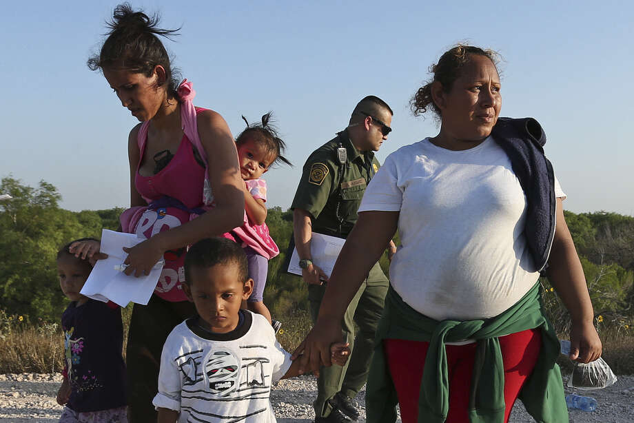 Some members of a group of immigrants — children in tow — who walked up to U.S. border agents southwest of McAllen are escorted to a transportation van. Photo: Photos By Jerry Lara / San Antonio Express-News / ©2014 San Antonio Express-News