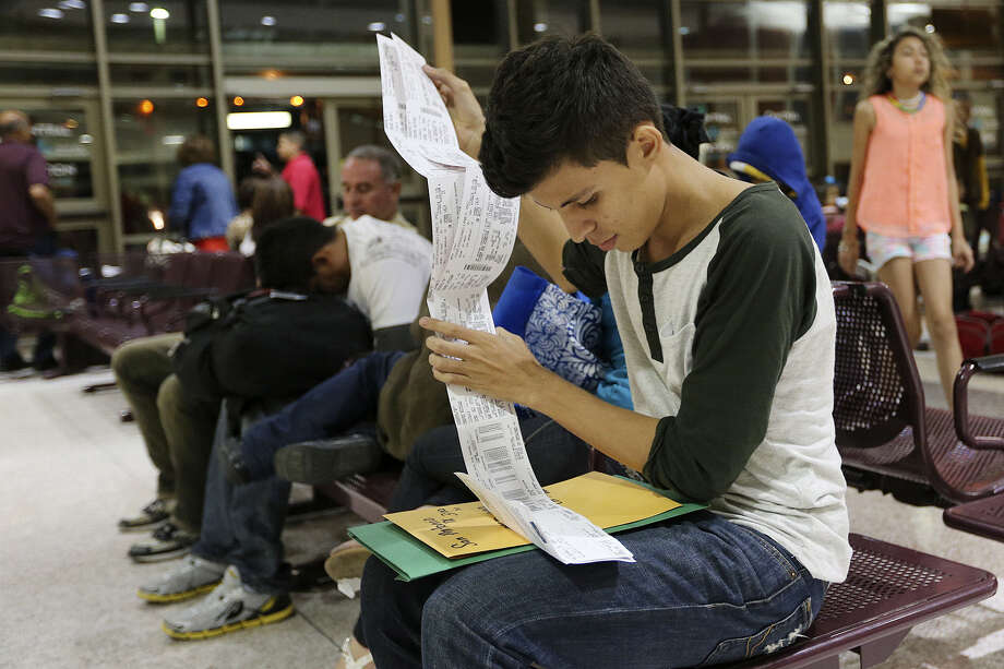 Bryan Chavez, 17, who's from El Salvador, checks out the bus ticket he received for Marine County, California, at the terminal in McAllen. Chavez, his father and his sister all trekked to the United States. He and his father were released by authorities, but his sister was detained. / ©2014 San Antonio Express-News