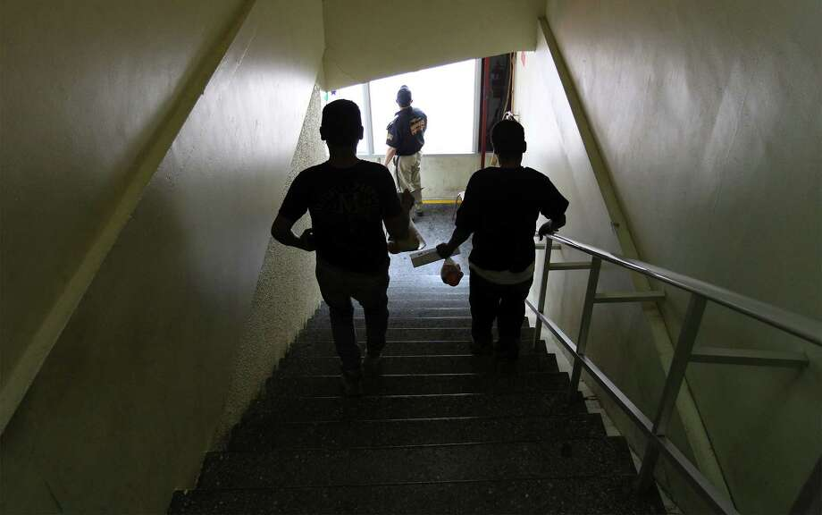 June 26, 2014, 1:30 p.m., Matamoros, Tamaulipas, Mexico - Two young Mexican men leave the Modulo de Atencion a Repatriados - a center to aid Mexicans who were deported from the United States - after getting paperwork from the Mexican government and some food and water. The two men were caught crossing over to Brownsville and were nabbed and sent back to Matamoros within minutes by border patrol according to one of the men who did not want to be identified. Photo: Kin Man Hui, San Antonio Express-News / ©2014 San Antonio Express-News