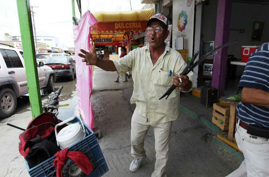 June 26, 2014, 12:30 p.m., Matamoros, Tamaulipas, Mexico - Alejandro Picasso attempts to sell windshield wipers near a market in Matamoros. Picasso claimed he need to sell the wipers to support his beer and marijuana habit. He rides his bicycle approximately 25 kilometers each day into town to work. Photo: Kin Man Hui, San Antonio Express-News / ©2014 San Antonio Express-News