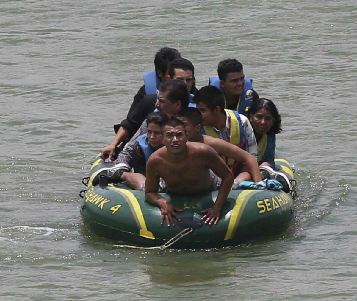 Using an inflatable raft, smugglers, carry immigrants across the Rio Grande near the international bridge in Roma. Law officials say higher-risk smuggling operations are moving into Starr County to avoid areas now saturated with officers.