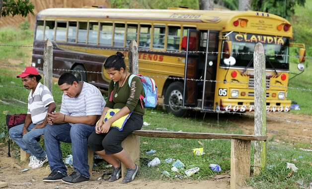 Nelsi Selena Bonilla, right, 18, who was separated from her husband after being deported from Mexico, sits dejected next to a man who was also deported, in Corinto, Honduras at the Guatemala border. Bonilla was dropped off at the small border town on Wednesday and has been sleeping outside a Red Cross station waiting for her husband in case he makes it back. Friday, June 27, 2014. Photo: Bob Owen, San Antonio Express-News / ©2013 San Antonio Express-News