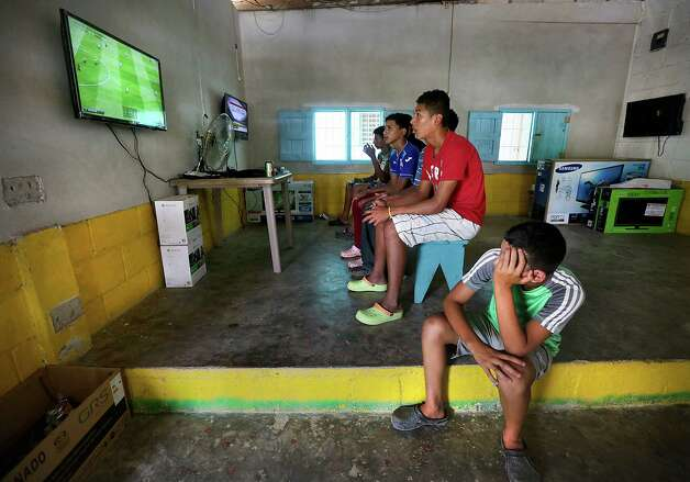 Teenage boys play soccer video games in the back room of a small snack store in Corinto, Honduras at the Guatemala border. Friday, June 27, 2014. The sparsely populated area is know for human and drug trafficking with many hidden crossing points into Guatemala. Photo: Bob Owen, San Antonio Express-News / ©2013 San Antonio Express-News