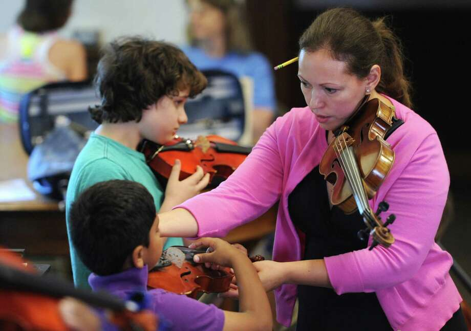 "Class instructor Alison Corigliano helps students Matthew Ratnauel, in the front, 7, of Ridgefield, and Ellery McFarland, 12, of Newtown, in the beginner class of the ""Summer Strings"" program at the Danbury Music Centre in Danbury, Conn. Monday, July 7, 2014.  Children and adults of all experience levels participate in the program, which is split into four groups each containing violins, violas, cellos and upright basses.  The classes are held three days a week for four weeks and the summer session culminates with a concert at Broadview Middle School on August 1. Photo: Tyler Sizemore / The News-Times"