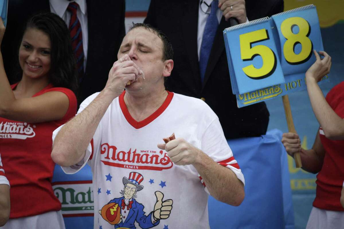 NEW YORK, NY - JULY 04: Joey Chestnut competes in the 98th annual Nathan's Famous Hot Dog Eating Contest at Coney Island on July 4, 2014 in the Brooklyn borough of New York City. Chesnut won his eighth straight Nathan's Hot Dog Eating Contest with 61 hot dogs. (Photo by Kena Betancur/Getty Images) ORG XMIT: 500073259