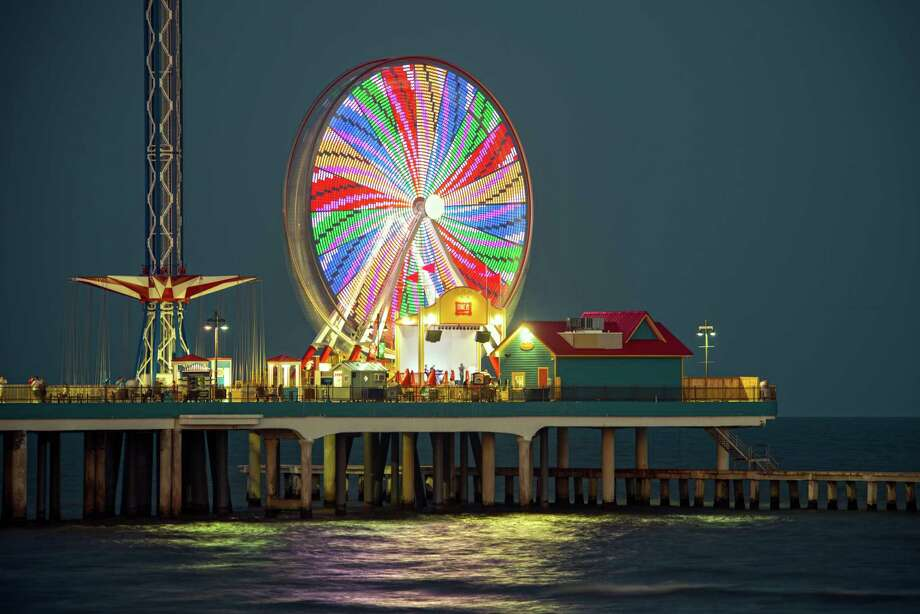 The Pleasure Pier lights up Galveston's Seawall at night and extends almost a quarter-mile out into the Gulf, with rides, games, restaurants and shops over the water. Photo: Hc / Vadim Troshkin