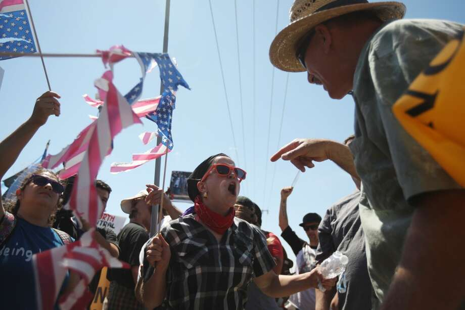 A protester who opposes arrivals of buses carrying largely women and children undocumented migrants for processing at the Murrieta Border Patrol Station and a counter-demonstrator (left) face off on July 4, 2014 in Murrieta, California. Earlier this week, protesters in the city turned away buses carrying about 140 immigrants that had been apprehended in Texas and flown to California for processing as Texas deals with an influx of immigrants. Federal officials estimate more than 50,000 minors, mostly from Central America, have been caught crossing the border since October 2013. Photo: David McNew, Getty Images