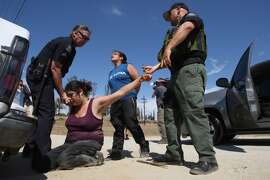 Counter-demonstrators to protesters opposing arrivals of buses carrying largely women and children undocumented migrants for processing at the Murrieta Border Patrol Station are detained on July 4, 2014 in Murrieta, California. Five people were arrested. Earlier this week, protesters turned away buses carrying about 140 immigrants in custody to the processing center. The immigrants are being flown from Texas where authorities are dealing with a with a crush of Central American children crossing the border to turned themselves in to border patrol agents. The influx is being fueled as people flee drug and violence problems in Central America with misinformation about immigration laws, and by drug cartels smuggling unaccompanied children of all ages across the border then leaving them on the U.S. side.