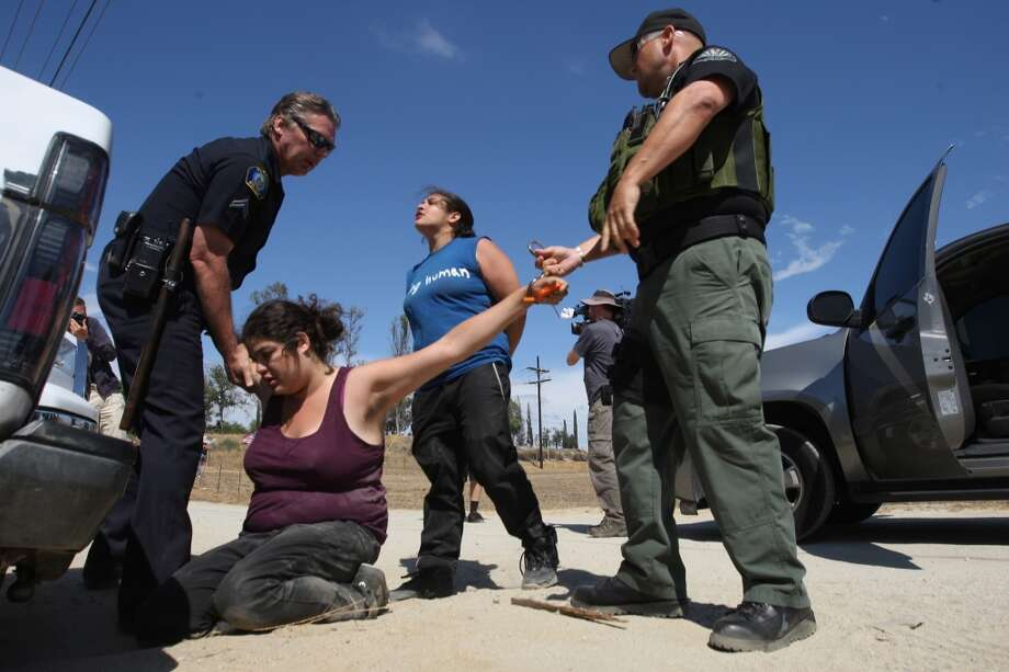 Counter-demonstrators to protesters opposing arrivals of buses carrying largely women and children undocumented migrants for processing at the Murrieta Border Patrol Station are detained on July 4, 2014 in Murrieta, California. Five people were arrested. Earlier this week, protesters turned away buses carrying about 140 immigrants in custody to the processing center. The immigrants are being flown from Texas where authorities are dealing with a with a crush of Central American children crossing the border to turned themselves in to border patrol agents. The influx is being fueled as people flee drug and violence problems in Central America with misinformation about immigration laws, and by drug cartels smuggling unaccompanied children of all ages across the border then leaving them on the U.S. side. Photo: David McNew, Getty Images