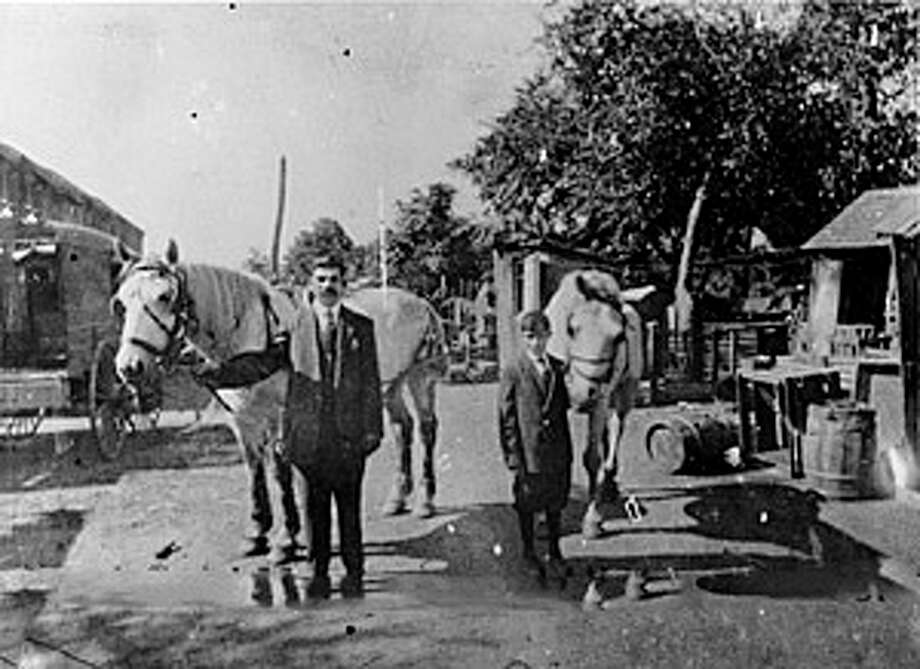 """Pop"" Mercurio and Dom Jr. hold the family's horses as they deliver fruits and vegetables to their customers via horse and wagon. The Mercurio's grocery business started in 1900. Courtesy: Fairfield Museum and History Center Photo: Contributed Photo / Fairfield Citizen"