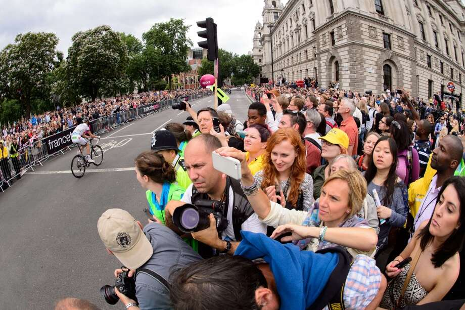 Spectators watch as riders enter Parliament Square heading towards the finish of the 155 km third stage of the 101st edition of the Tour de France. Photo: LEON NEAL, AFP/Getty Images
