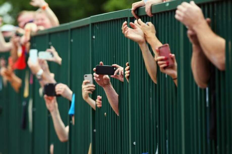 Fans try to take photos through a fence on the third stage of the 2014 Tour de France. Photo: Bryn Lennon, Getty Images