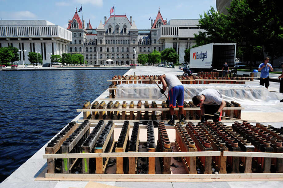 Workers with Alonzo Fireworks set up the tubes that will hold the fireworks on Thursday, July 3, 2014, at the Empire State Plaza in Albany, N.Y.  The workers were getting the tubes ready for the fireworks show that will be part of Friday's Independence Day celebration at the Plaza.  (Paul Buckowski / Times Union) Photo: Paul Buckowski, Albany Times Union / 00027615A