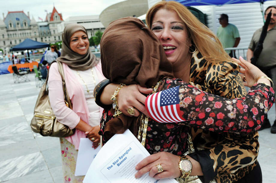 New U.S. citizen Natasha Naji of Albany, a native of Iraq, right, hugs her daughter Noor Murad, center, following a naturalization ceremony on Friday July 4, 2014, at the Empire State Plaza in Albany, N.Y. At left is refugee volunteer Zainab Chaudhry. (Cindy Schultz / Times Union) Photo: Cindy Schultz, Albany Times Union / 00027120A