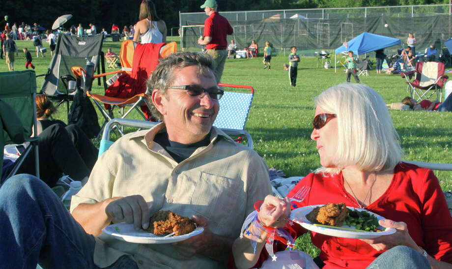 Peter and Helen Yorinski of Washington seem to have life in proper perspective July 5, 2014 as they feast and relax during the picnic preceding Washington's annual Fourth of July fireworks show on the campus of Shepaug Valley High School. Photo: Walter Kidd / The News-Times Freelance