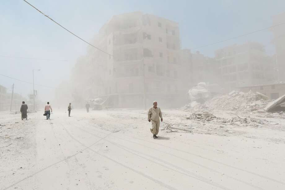More bombs for Aleppo:Syrians walk through a huge cloud of dust following a reported barrel-bomb attack by government forces in the   Tariq al-Bab neighborhood of Aleppo. Photo: Zein Al-rifai, AFP/Getty Images