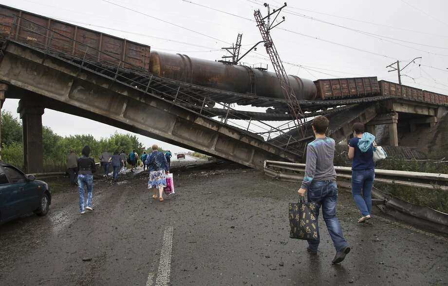 An 11-car freight train sits precariously atop a destroyed railroad bridge leading into the city of Donetsk, Ukraine, near the town of Novobakhmutivka. Photo: Dmitry Lovetsky, Associated Press