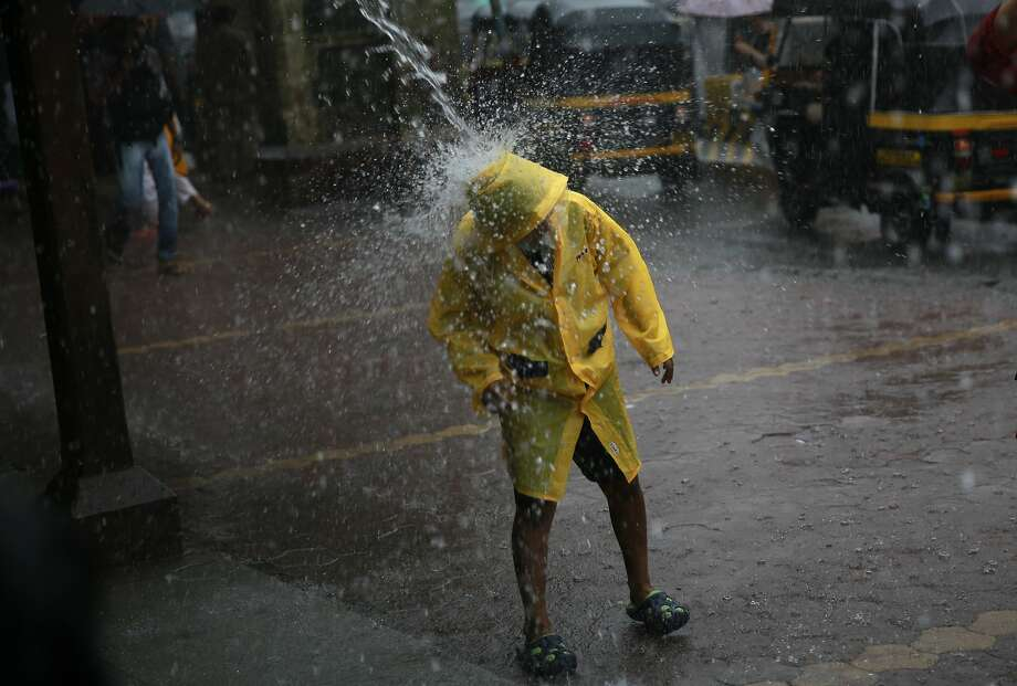 As if justifying his decision to wear rain gear, a boy stands in a stream of water pouring from a roof during monsoon rains in Mumbai. Photo: Rafiq Maqbool, Associated Press