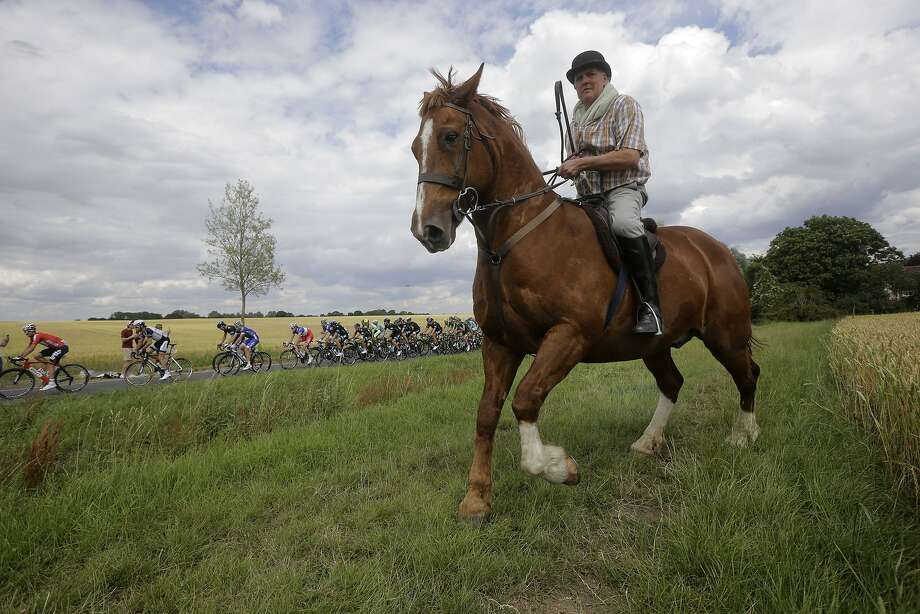 Four-legged vs. two-wheeled transportation:A English equestrian rides alongside the pack during the third stage of the Tour de France between 
