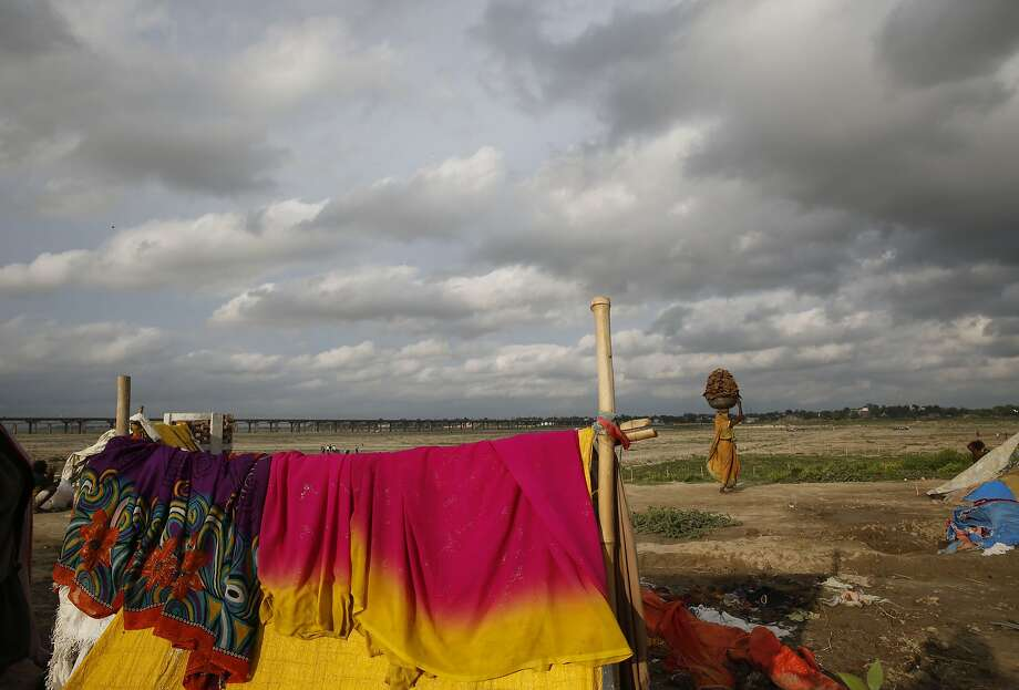 Saris dry on a homeless family's river-side shelter in Allahabad, India, as a woman balances 
