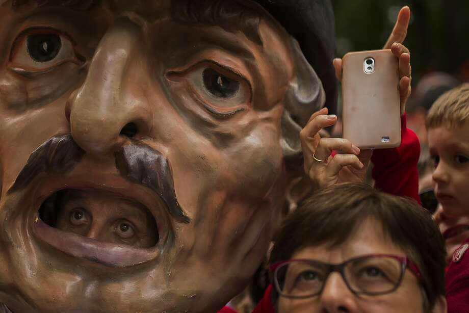 The mouth is the window to the eyes: A big-headed celebrant watches the San Fermin procession in Pamplona, Spain, with more normally proportioned revelers. Photo: Andres Kudacki, Associated Press