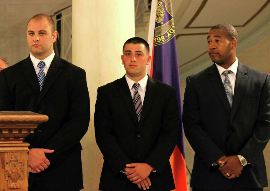 Cole Merryman, left, Nicholas Ottati, center, and James Plowden, right, are sworn in as Schenectady police officer recruits Monday, July 7, 2014, at City Hall in Schenectady N.Y. (Selby Smith / Special to the Times Union) Photo: Selby Smith / 00027636A