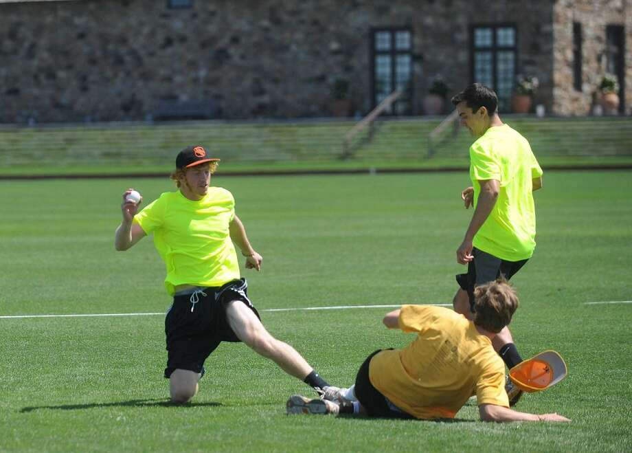 Team Traffic Cones' Jimmy Hannigan, left, and Drew Gasparrini, right, try to get team Carlyle Group's Sperry Edawrds out at second base during Saturday's town-wide Greenwich Wiffle Ball Tournament at the Greenwich Polo Club on July 21, 2012. Photo: Lindsay Niegelberg