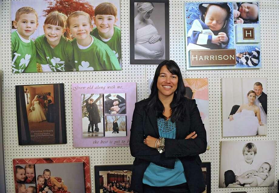 Photographer Christina Primero stands in front of a wall displaying her work in her home studio Friday, June 20, 2014 in Albany, N.Y.  (Lori Van Buren / Times Union) Photo: Lori Van Buren / 00027414A